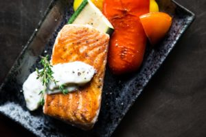 cooked fish on a black plate with vegetables and white sauce