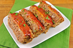 four slices of meatloaf on white plate