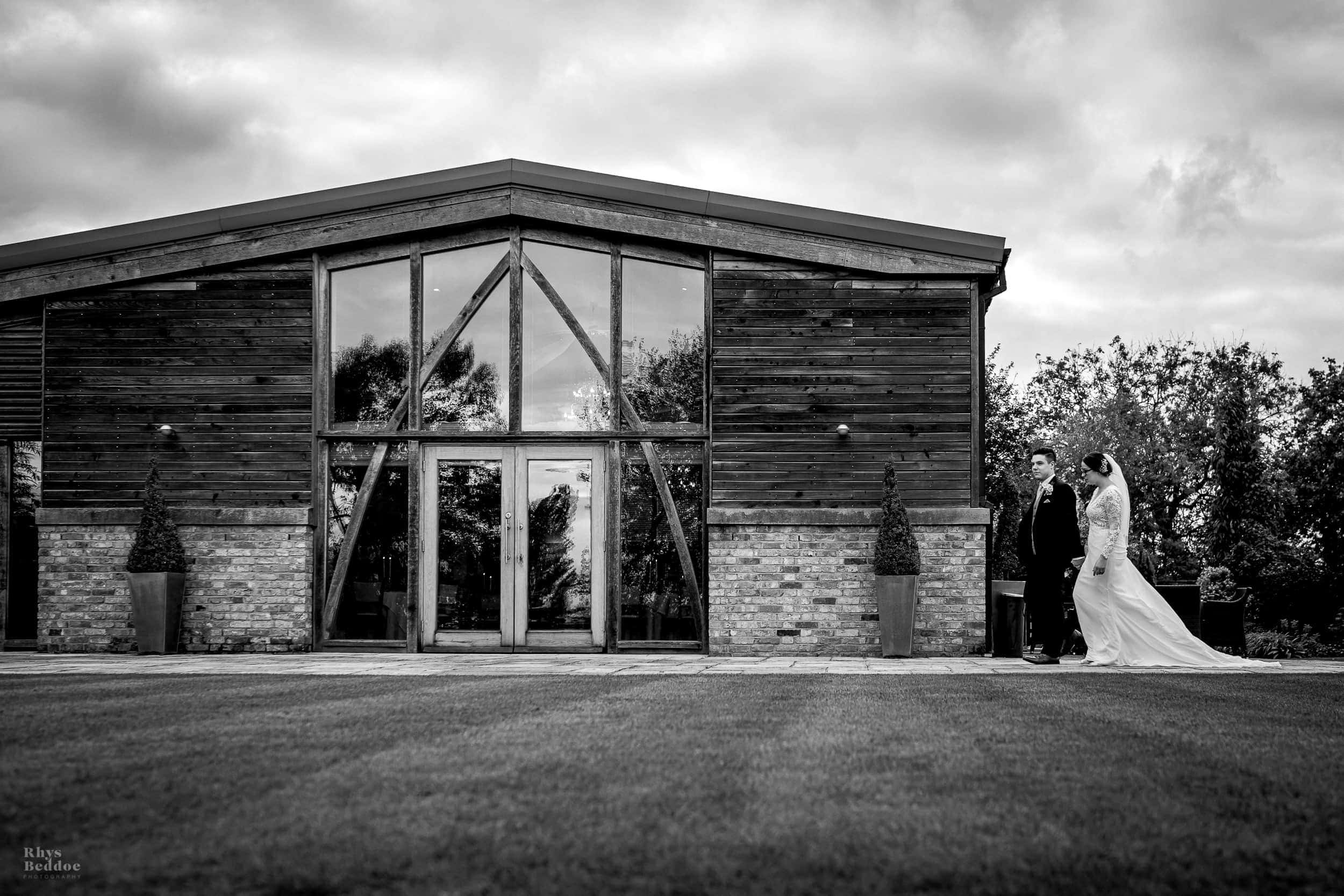 bride and groom walking outside Mythe Barn