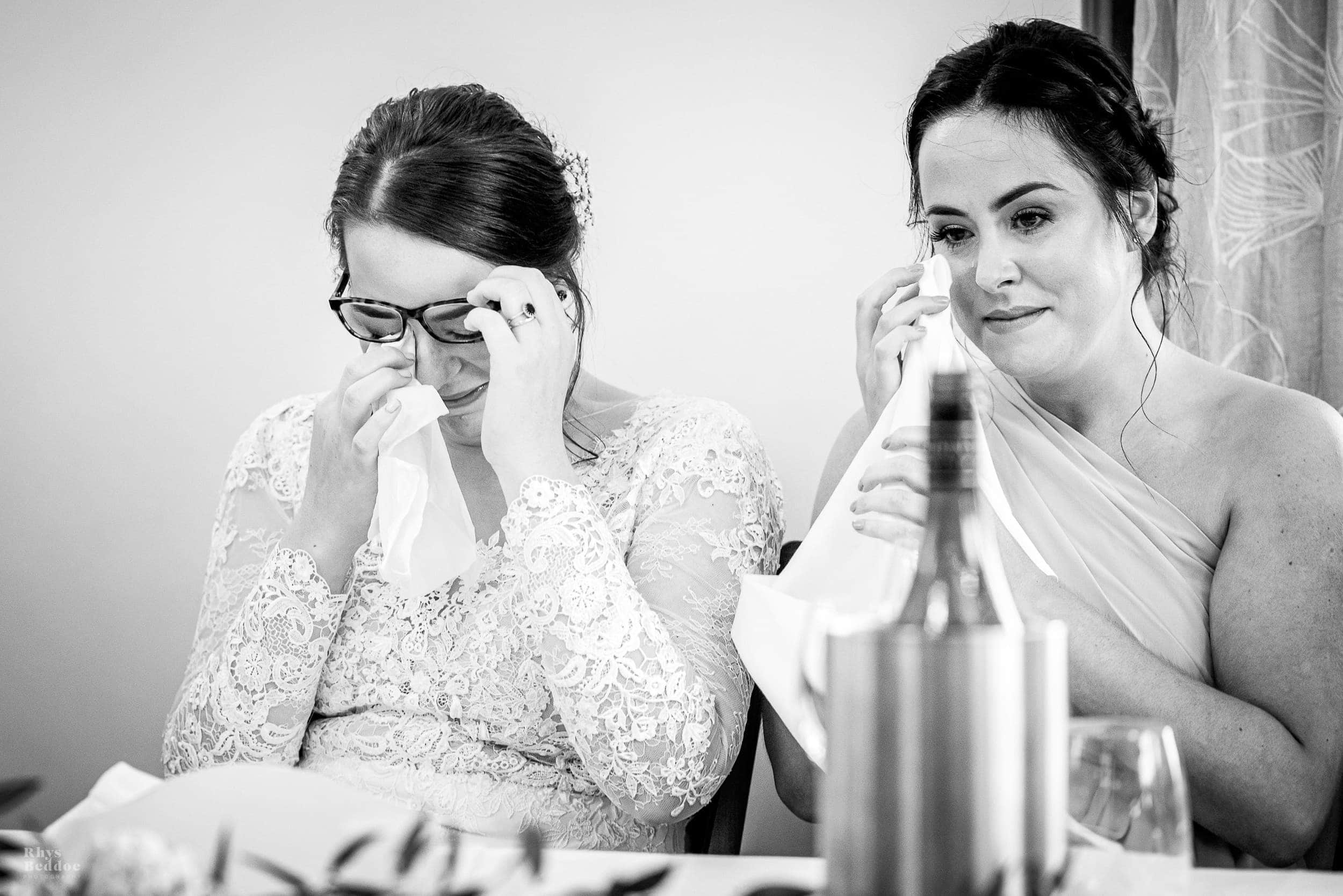Bride and sister crying with laughter during speech at mythe barn