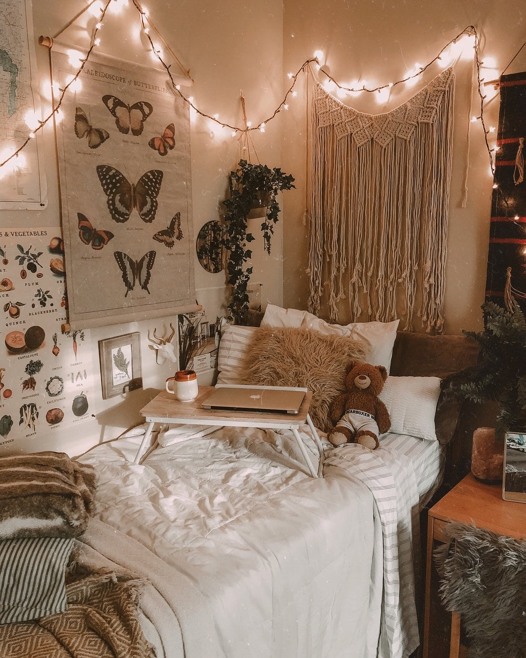 girl dorm with macrame, butterfly poster, bed desk, throw pillows and teddy bear + string lights