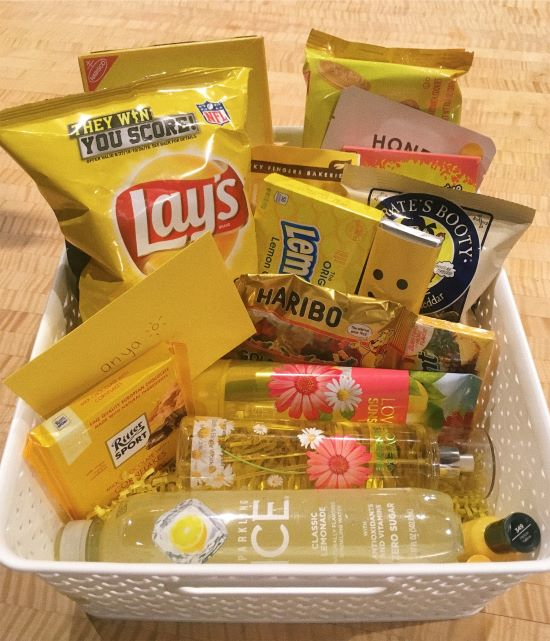 white gift basket with yellow drinks and food - sunshine box example