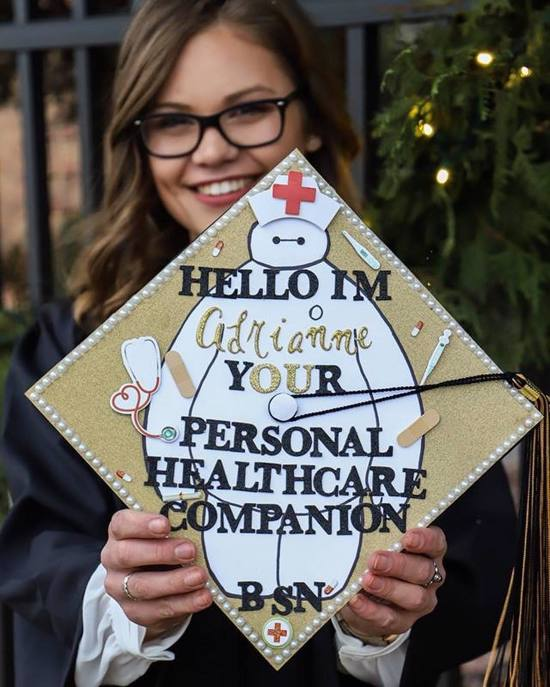 """gold glitter BSN grad cap decorated with Baymax from Big Hero 6 movie wearing a nurse hat and words """"hello I'm adrianne your personal healthcare companion"""""""