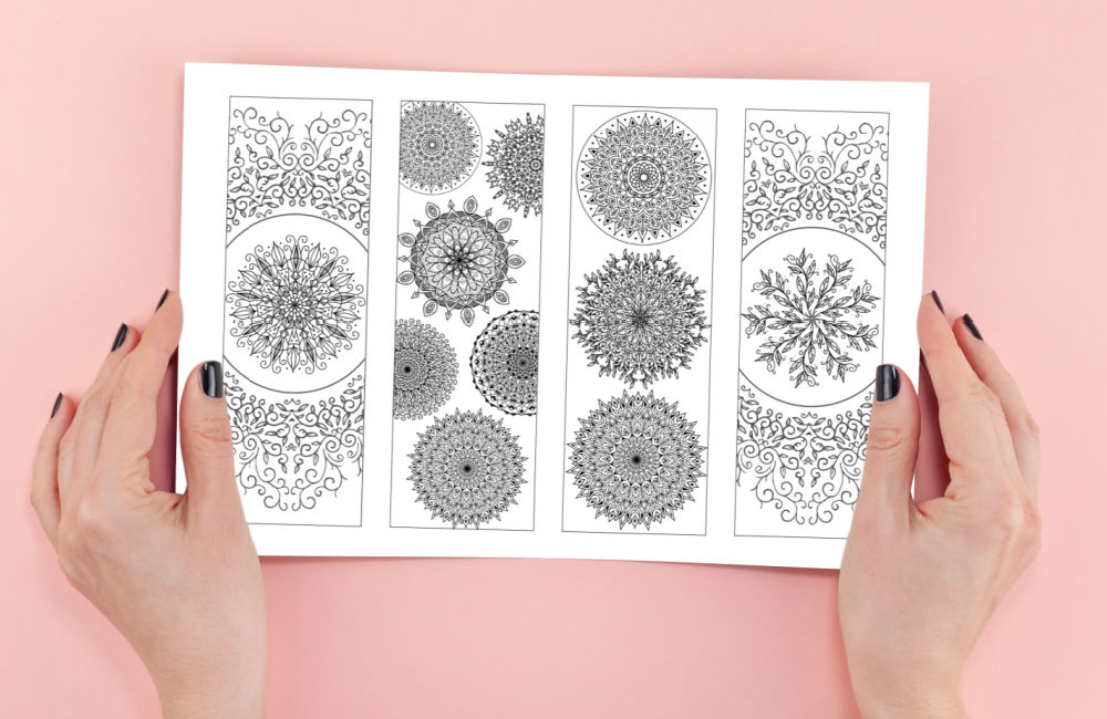 printable mandala bookmarks to color being held by woman's hands with black nail polish
