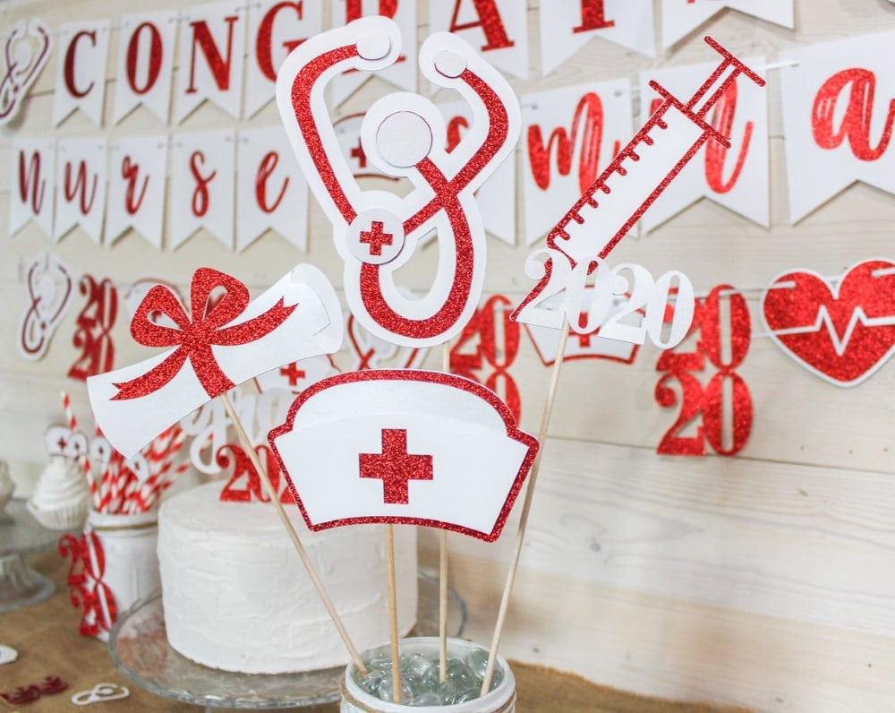 paper cutouts of diploma, stethoscope, nurse hat, and syringe with red glitter accents