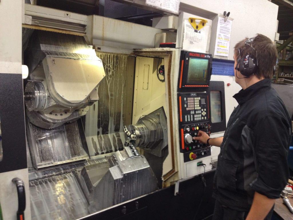 Dette maskineringssenteret har flere kjokser og kan jobbe i mange ulike akser. Det kan produseres komplekse deler helt ferdig i en automatisk prosess. Maskinen kan også kjøres ubemannet på kveld og natt. Operatøren kan da følge med på internett via PC-en hjemme, hva som skjer på maskinen.