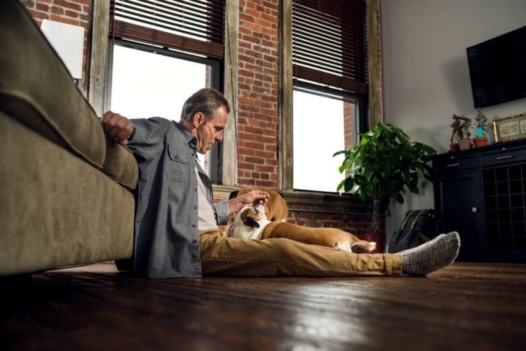 white man petting a dog on a wooden floor