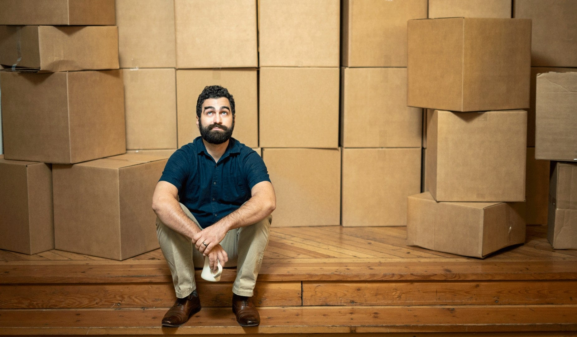 white man in blue polo in front of cardboard boxes