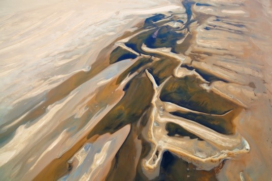 Image: Theo's desert from above with flowing colors of mauve, blue-grey and camel
