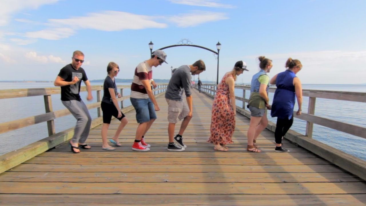 Image: Screen capture from 100 People of Dance, a bunch of people dancing on a pier.