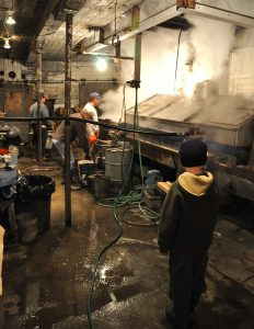Image: Child looking on as people work around the evaporator rig at the sugar house