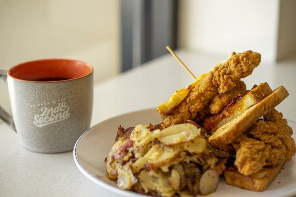 Fried chicken sandwich next to a coffee mug with a side of hash browns