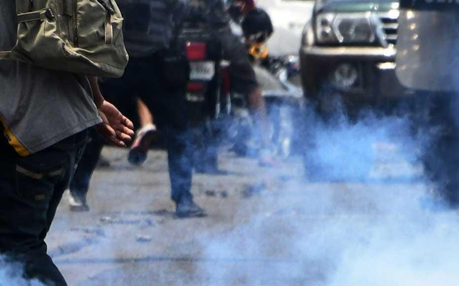 Riot Police officers use tear gas to disperse protesters near the premises of Globo radio and TV, during the arrest of Honduran journalist David Romero, who barricaded during four days at the station resisting his capture in Tegucigalpa, on March 28, 2019.