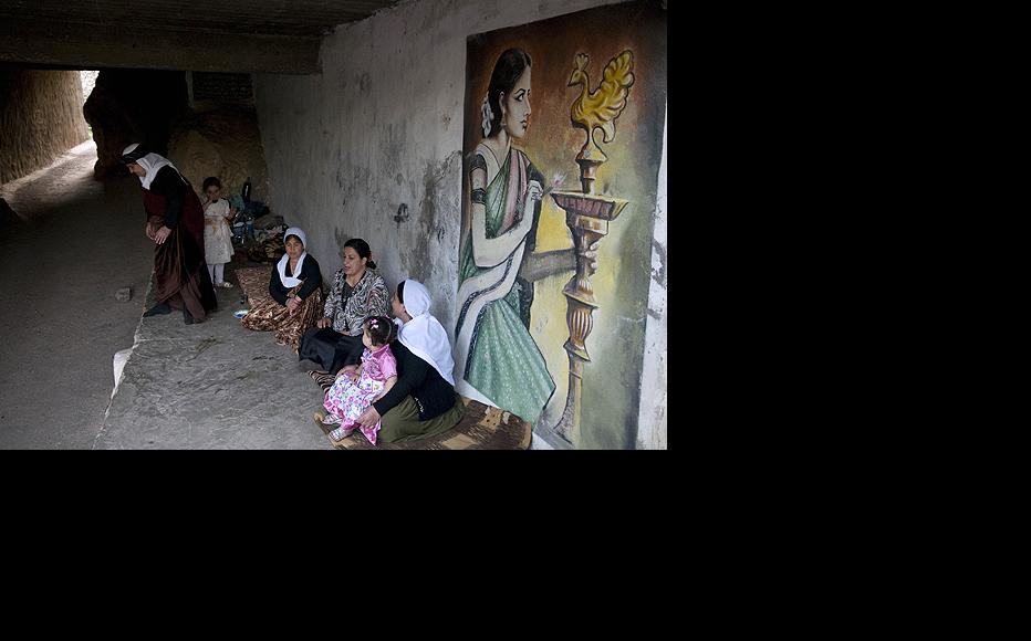 Yezidi women sit in the cavernous Lalish Temple near a painting of a Yezidi woman praying to the Peacock Angel. The Peacock Angel, known as Melek Tawus, is the most sacred of the seven holy beings of the Yezidi faith.