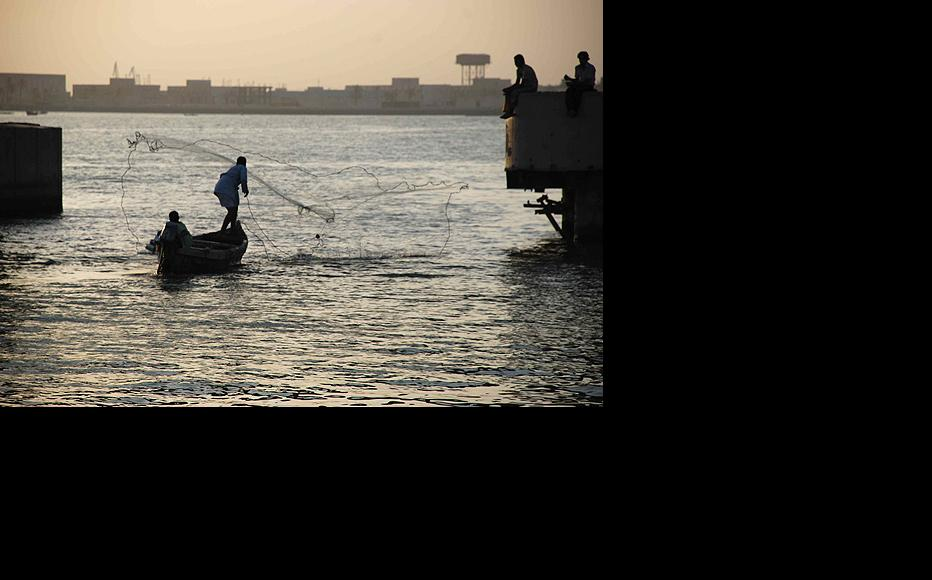 A fisherman cast a gill net from the bow of a traditional wooden boat as the Karma river drains into the Tigris a few kilometres north of Basra. (Photo: Ali Abu Iraq)