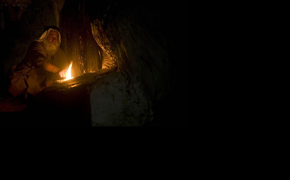 An elderly Yezidi man burns a sacred candle in the Lalish Temple. Yezidi believe in the purity of the four elements - earth, wind, fire and water - and lighting a torch or candle on New Year's day is done to welcome the upcoming year.