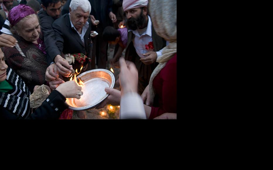 Men and women light candle wicks dipped in oil and throw them in a copper plate as part of the Yezidi New Year celebration on April 14 in Lalish Temple. Yezidi welcome the New Year by lighting candles and flames.