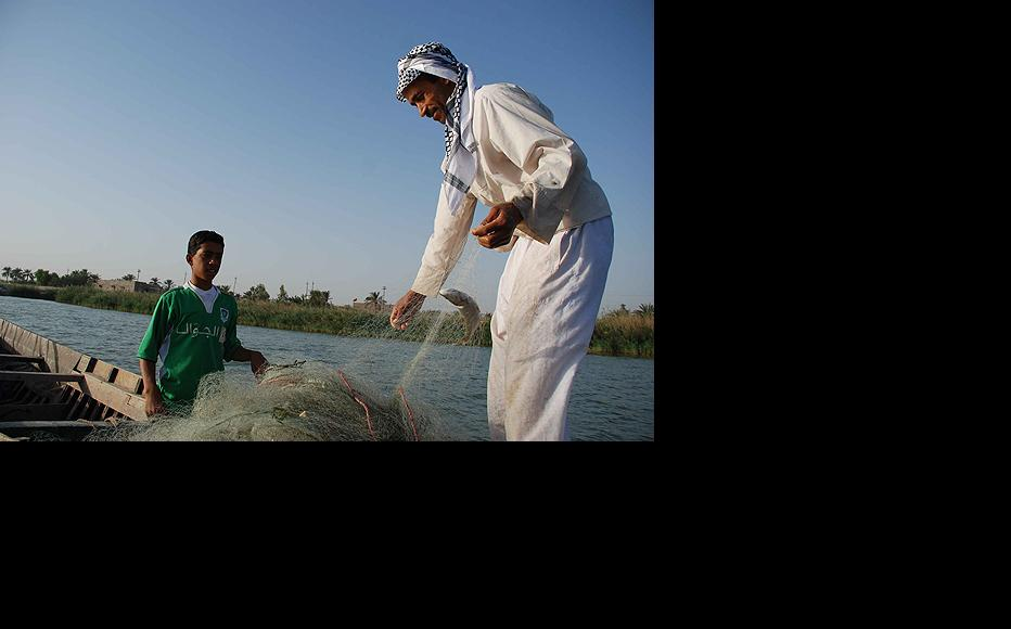 A boy and his father collect fish from a gathered net during a typical day of fishing near the city of Basra. (Photo: Ali Abu Iraq)