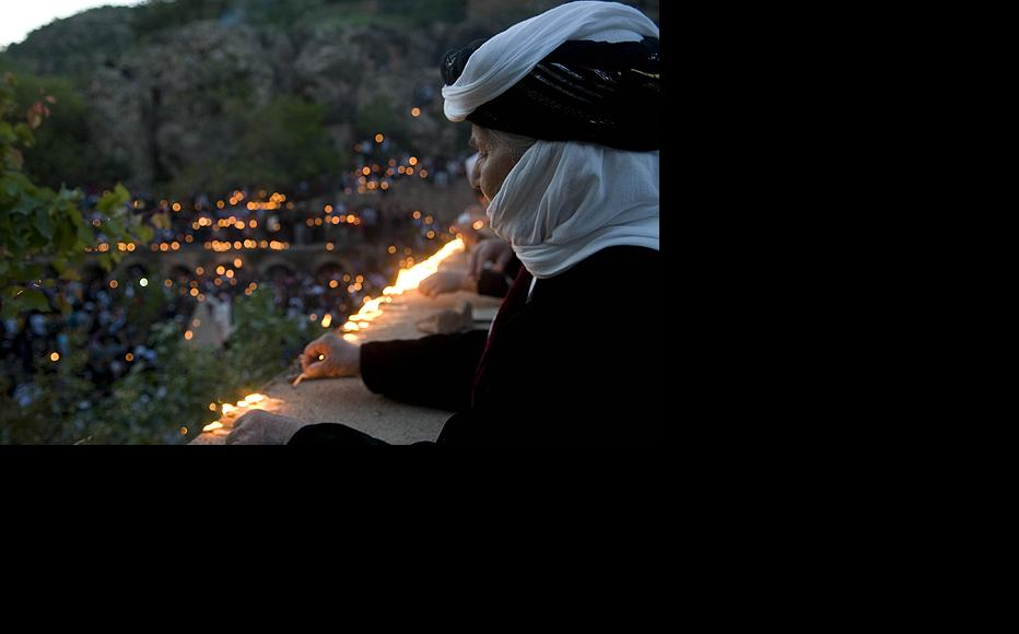 A Yezidi woman lights an oil-soaked candle and places it along a ledge overlooking the holy Lalish Valley in Iraqi Kurdistan north of the city of Mosul. The Lalish Valley is home to the religion's most sacred temple and the tomb of the revered Sheikh Adi Ibn Musafir.