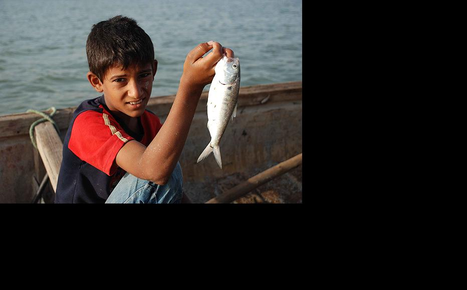 A young man holds up a fish known locally as saburra. Like many of the fish species common to the area's endangered waterways, the local saburra catch has been declining in recent years due to factors such as oil exploration and over-fishing. (Photo: Ali Abu Iraq)
