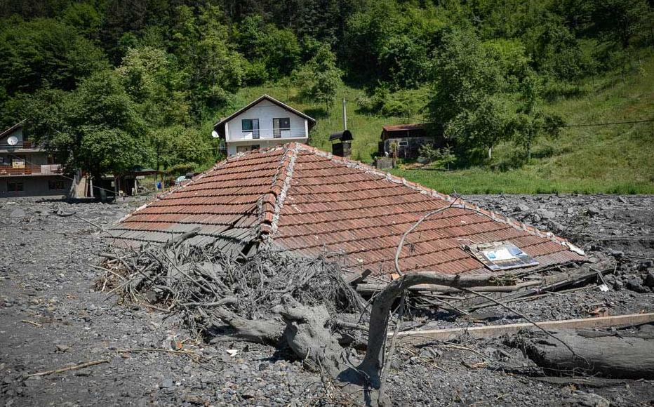 A house almost completely submerged in mud. Topcic Polje, May 21, 2014.