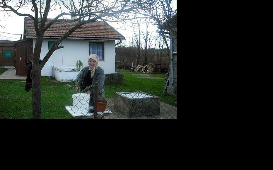 Sejda Morica plants flowers in front of her house. (Photo: IWPR)