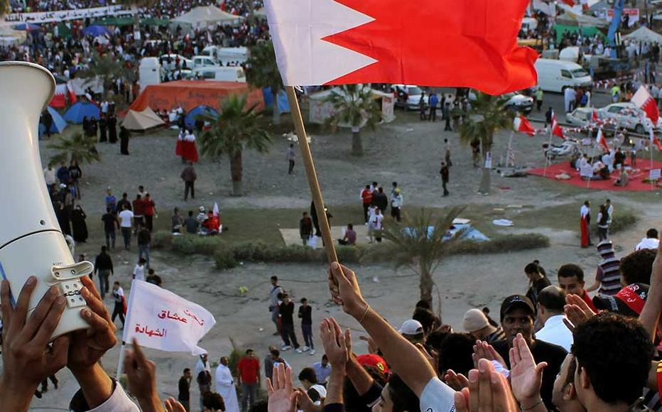 Anti-government protesters wave flags and demonstrate at Pearl Roundabout on February 20, 2011 in Manama, Bahrain.