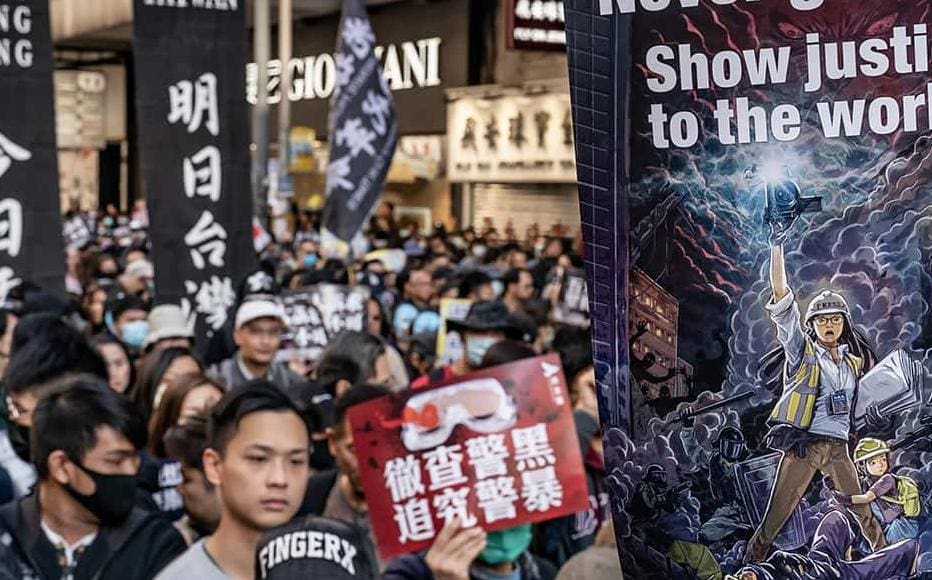 Pro-democracy protesters march on a street as they take part in a demonstration on December 8, 2019 in Hong Kong, China.