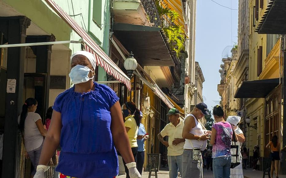 A shopper wearing a face mask walks in Old Havana, on March 27, 2020.
