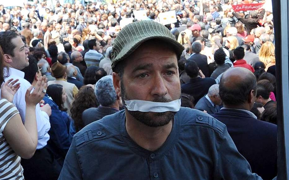 A Tunisian journalist holds a TV frame on April 25, 2012 during a sit-in outside the municipal theatre in Tunis to protesting silencing Tunisian Television journalists.