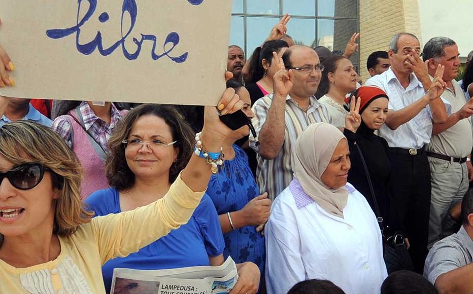 Tunisian journalists of Assabah daily hold signs calling for freedom of the press during a protest in Tunis on September 11, 2012.