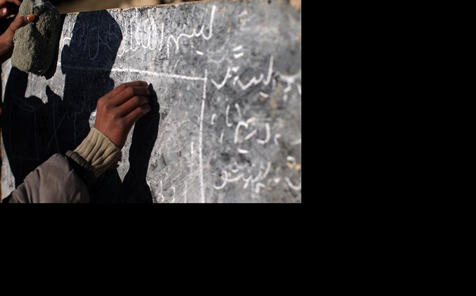An Afghan boy writes on a chalkboard at a rural school in Afghanistan. (Photo: Spencer Platt/Getty Images)