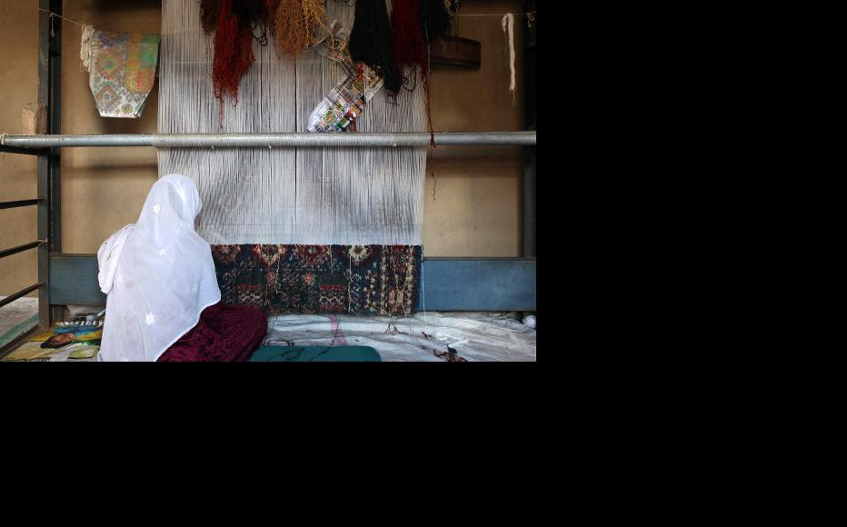 An Afghan woman weaving a rug. (Photo: Heidi Agostini)