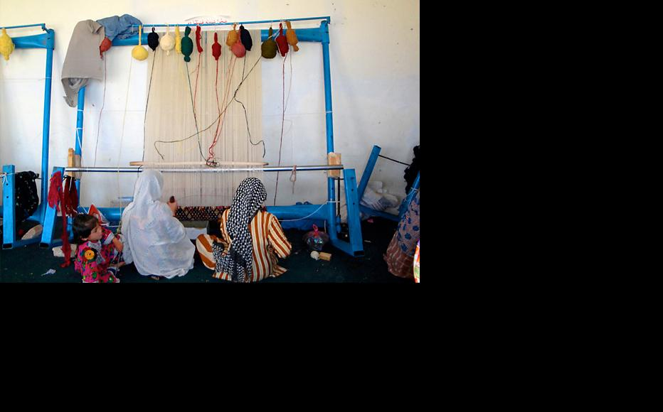 Afghan women prepare to weave a traditional rug. (Photo: Canada in Afghanistan/Flickr)