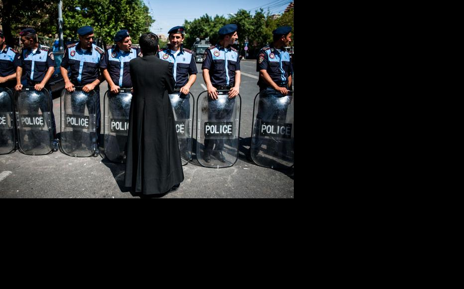 A priest talks to police who have formed a cordon on Baghramyan Avenue. June 24, 2015. (Photo: Nazik Armenakyan)