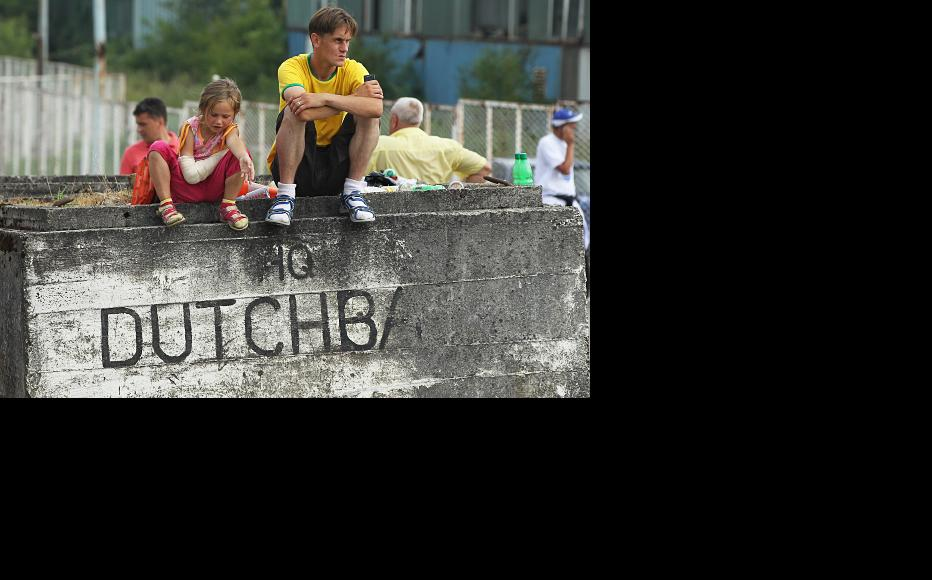 Children sit on a concrete block outside the former base of the Dutch peacekeepers at Srebrenica, following the mass funeral of 613 victims. July 11, 2011. (Photo: Sean Gallup/Getty Images)