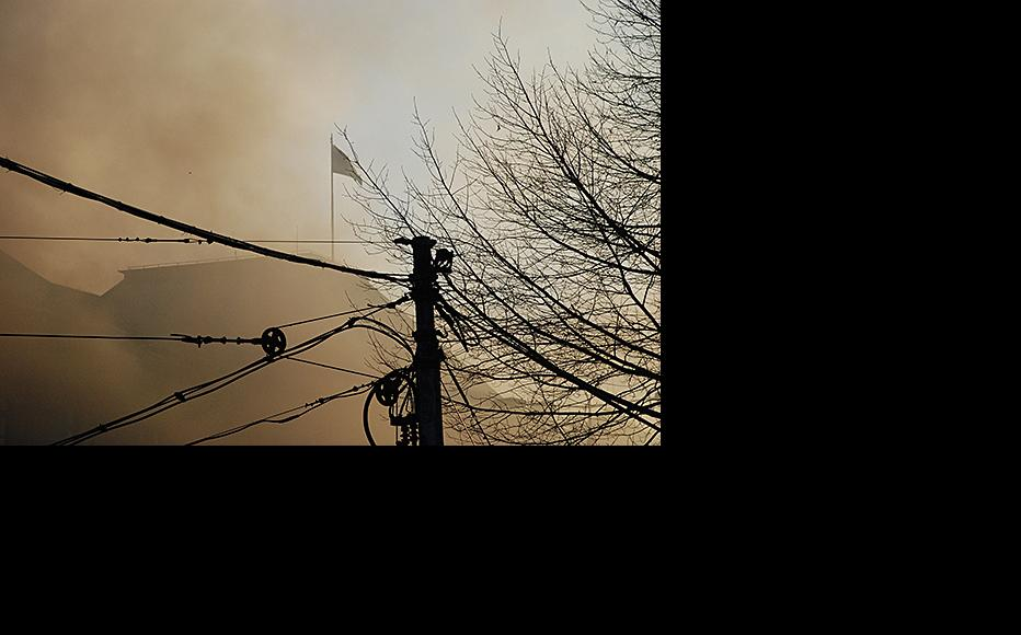 The flag of Bosnia and Herzegovina files above the burning Presidency. February 7, 2014. (Photo: Jim Marshall)