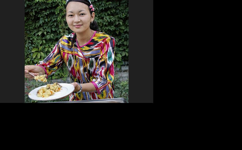 A woman is serving plov at a reception on behalf of the Uzbek Embassy in Almaty, Kazakstan. (Photo: Aziz Mamirov)