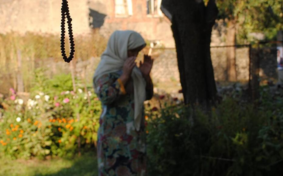 A woman from Tivi village praying.
