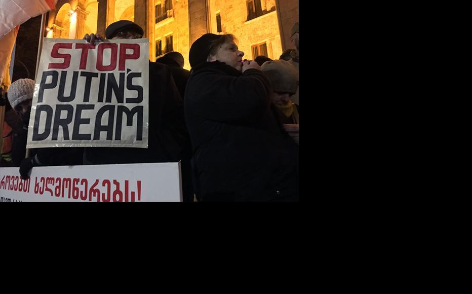 A demonstrator holding a poster referring to the ruling Georgian Dream Party, accused by protestants of siding with Putin's government. (Photo: Temur Kighuradze/IWPR)