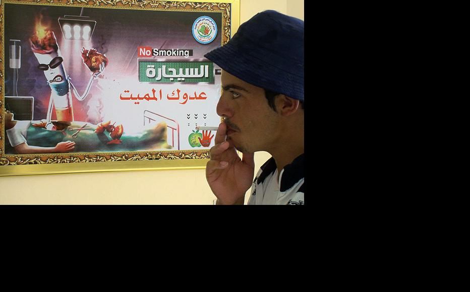 "A student at Qadisiyah University in Diwaniya takes a drag from a cigarette in front of an anti-smoking sign that reads ""Cigarettes are a deadly enemy"". A recent ban on smoking in the province's government offices has been criticised by locals. (Photo: Imad al-Khuzaei)"