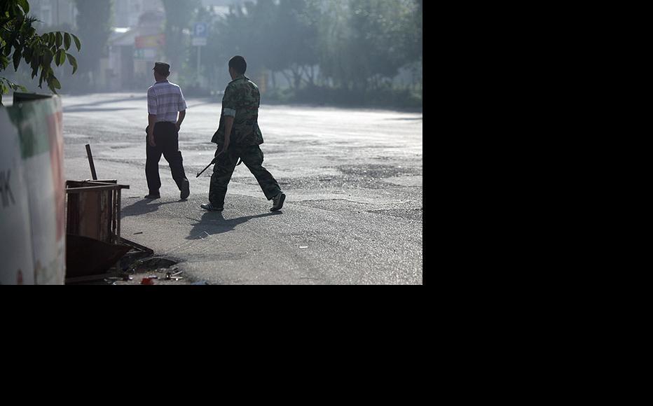 Armed men roam the streets of Osh as a pall of smoke settles over the city. (Photo: Inga Sikorskaya)