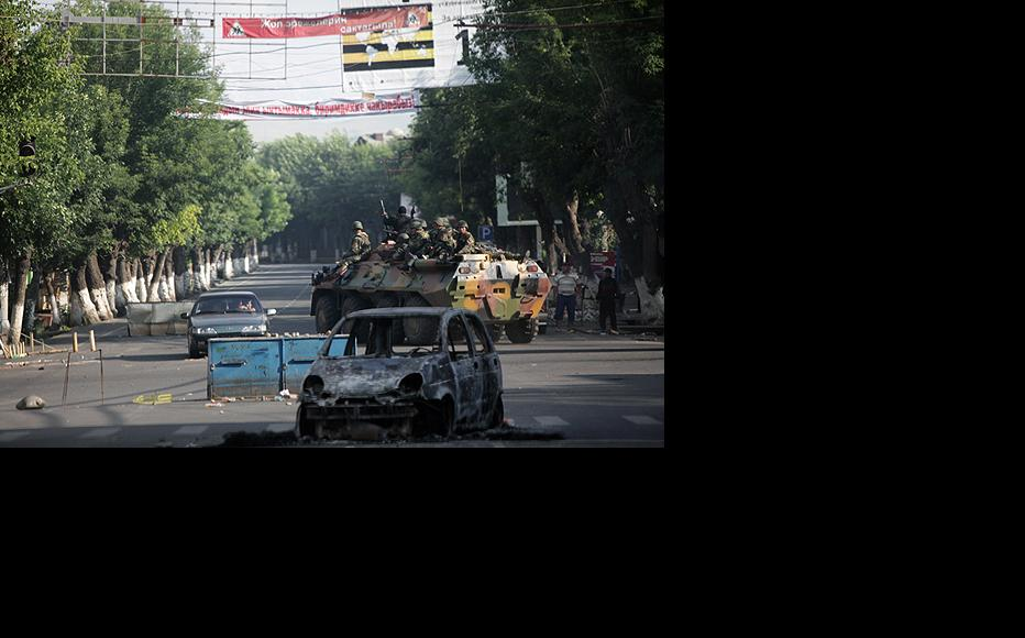 Kyrgyz security forces drive past a burnt-out car blocking a road in Osh. (Photo: Inga Sikorskaya)