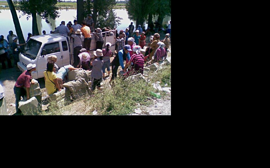 These people, just inside Kyrgyzstan, are being handed goods which they will take over the border into Kazakstan for a fee. (Photo: IWPR)