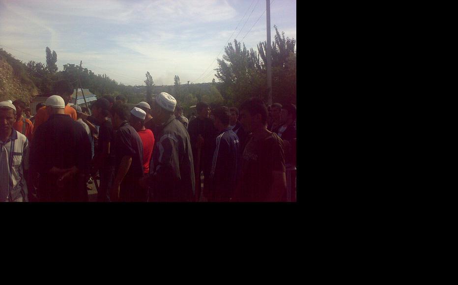 Young Uzbeks armed with sticks carry rocks to strengthen their roadblock. (Photo: Isomidin Ahmedjanov)