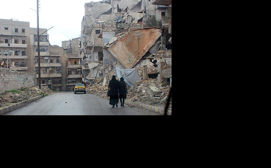 Two teachers pass through a street filled with demolished buildings on their way to a school in the Ansari neighbourhood of Aleppo. Photographer: Salah al-Ashqar