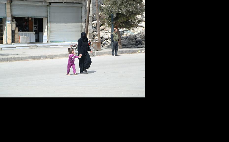 A woman and her daughter cross the street close to ruins in Aleppo's Al-Marja neighbourhood. (Photo: Hussam Kuwaifatiyeh)