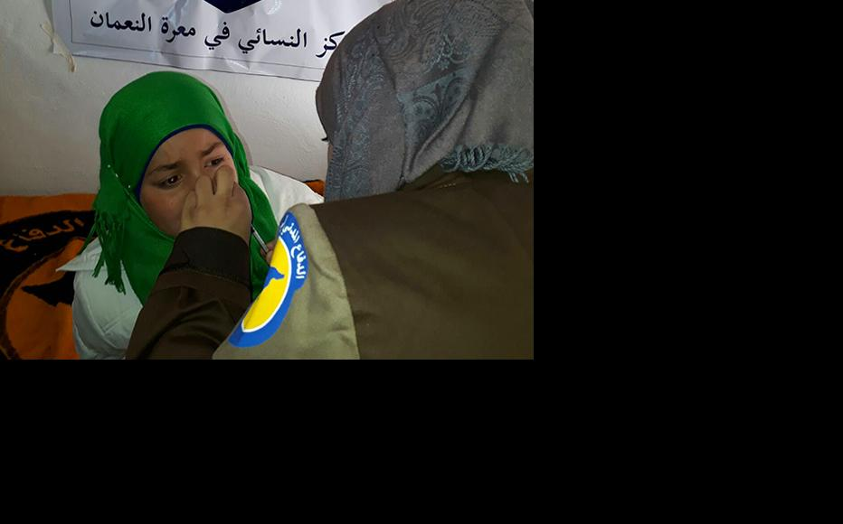 A paramedic examines a child at the Syrian civil defence centre in Maarrat al-Nu'man. (Photo: IWPR)