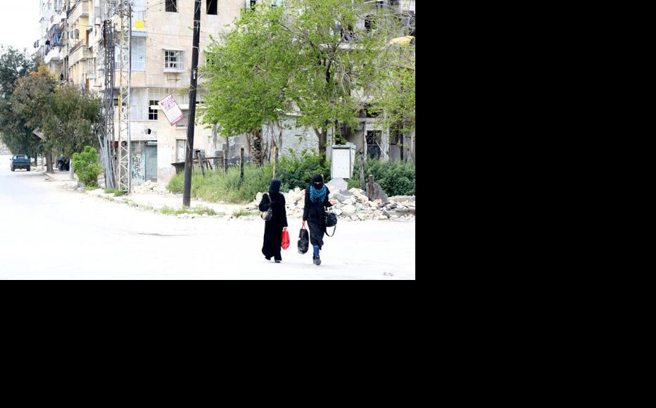Two women walk through the al-Shaar neighbourhood. (Photo: Hussam Kuwaifatieh)