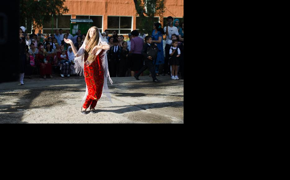 A high-school student performs a national Tajik dance in front of the crowd. (Photo: Roman Buryak)